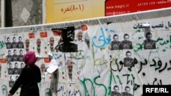 An Iranian woman walks past campaign posters in Tehran on June 8.