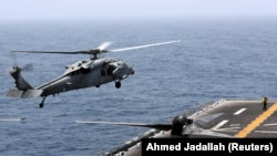 AT SEA -- An MH-60S Sea Hawk lands on the flight deck of USS Boxer (LHD-4) in the Arabian Sea off Oman, July 16, 2019