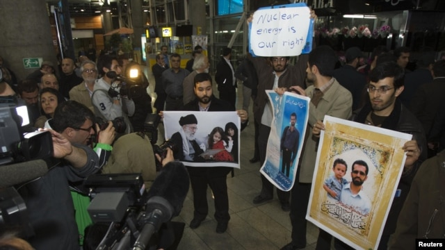 Iranian students hold up pictures of Iranian scientist Mostafa Ahmadi-Roshan, who was killed in a bomb blast on January 11,  as they wait for the arrival of the IAEA delegates at Tehran's Imam Khomeini International Airport on January 29.