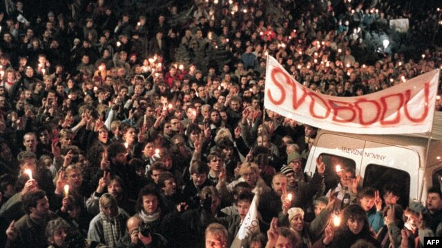 "Thousands of people gather under a banner reading ""Liberty"" flashing Victory signs in an anti-Communist rally 27 November 1989 in Prague."