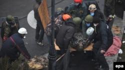 Протестующие уносят одного из раненных в столкновениях. Киев, 20 февраля 2014 года.