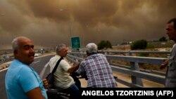 Люди дивляться на дим від пожежі в курортному місті Кінета біля Афін, Греція, 23 липня 2018 року