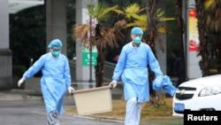 چیني روغتیاپالان د ویروس د نمونې د لېږد پر مهال.