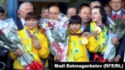 Олимпийские чемпионки Майя Манеза (слева), Зульфия Чиншанло (в центре), Светлана Подобедова в алматинском аэропорту после возвращения из Лондона, где проходили Игры. 8 августа 2012 года.