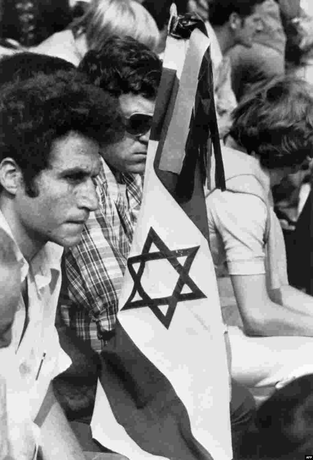 Members of the Israeli team holding an Israeli flag mourn during a memorial ceremony held at Olympic Stadium on September 6, 1972.