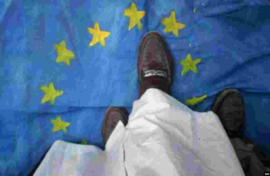 A man in Pakistan treads on an EU flag during a February demonstration in Karachi (epa) - In March, moderate Bosnian Muslim leader Reisu-UI-ulema Mustafa Ceric told RFE/RL that European Muslims can play a unique role in bridging the gap between the Islamic world and the West.