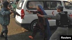 Полицейские уводят женщину от места сегодняшнего теракта