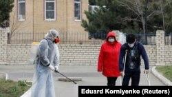 Специалист в защитном снаряжении дезинфицирует территорию местной больницы в городе Михайловске Ставропольского края, 3 апреля 2020 года