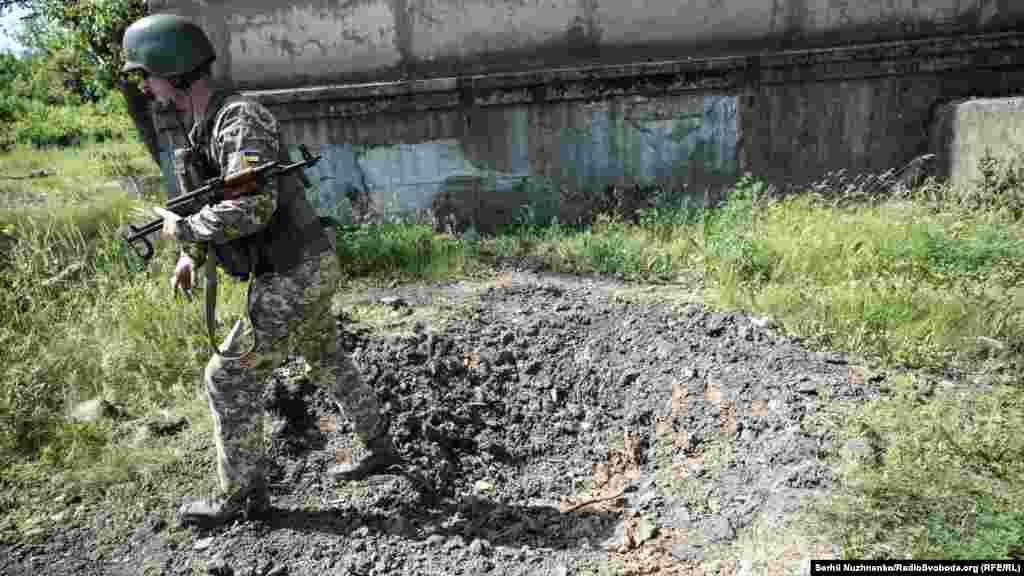 Російські гібридні сили регулярно обстрілюють контрольовану ЗСУ територію із заборонених Мінськом видів озброєння, заявляють українські військові, про що свідчить і ця вирва