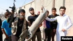 An IS militant (left) stands next to residents as they hold pieces of wreckage from a Syrian war plane after it crashed in Raqqa in September, 2014.