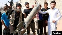 Një pjesëtar i militantëve dhe banorë i tregojnë pjesët e aeroplanit ushtarak të rrëzuar