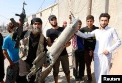Сирияда құлаған ұшақ бөлшегін ұстап тұрған «Ислам мемлекеті» тобының өкілі.