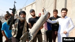 An IS militant (left) stands next to residents as they hold pieces of wreckage from a Syrian war plane after it crashed in Raqqa. (file photo)