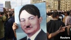 Демонстрант өзгертілген Хосни Мүбәрәктің портретін ұстап тұр. Каир, 31 қаңтар 2011 жыл