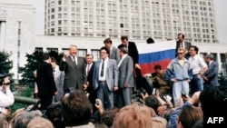 Russian President Boris Yeltsin (left) stands on top of an armored vehicle parked in front of the Russian Federation building in Moscow on August 19, 1991.