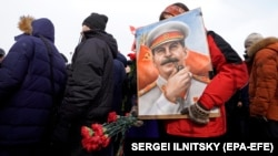 A Russian communist carries a portrait of former Soviet leader Josef Stalin during a wreath-laying ceremony at his tomb to mark the 65th anniversary of his death, near the Kremlin wall in Moscow's Red Square on March 5.
