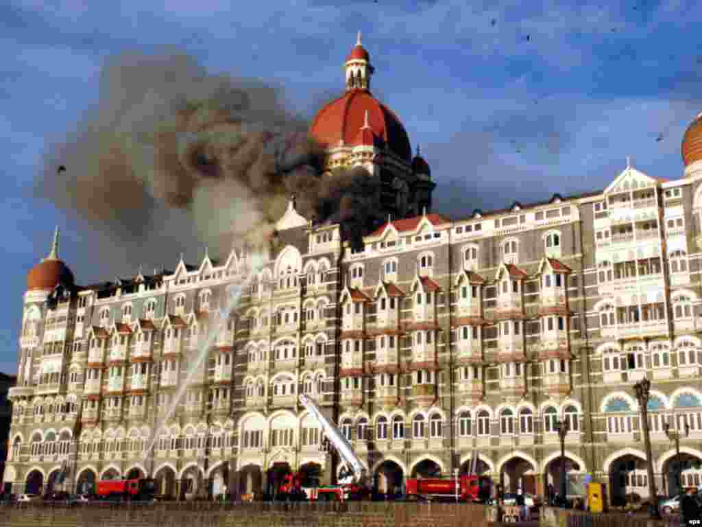 Firefighters attempt to put out the flames as smoke rises from the Taj Mahal hotel, which was stormed by the terrorists.