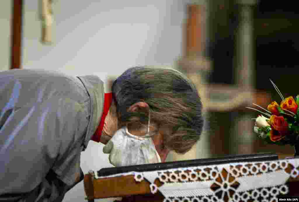A worshiper wearing a face mask kisses an icon during the Orthodox Christian Easter service at a church in Zenica, central Bosnia.