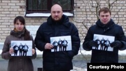 """In a Facebook photo, three people, including Uladzimer Labkovich (right), hold up photos of the """"Byalyatski Three"""" activists, who are themselves brandishing images of jailed rights activist Ales Byalyatski."""