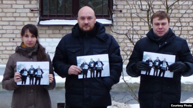 "In a Facebook photo, three people, including Uladzimer Labkovich (right), hold up photos of the ""Byalyatski Three"" activists, who are themselves brandishing images of jailed rights activist Ales Byalyatski."