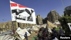"""Antigovernment protesters sit outside their tents below a flag that says """"No to the constitution,"""" on Tahrir Square in Cairo on December 10."""