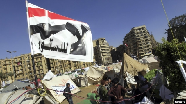 Antigovernment protesters sit outside their tents below a flag that says 'No to the constitution,' on Tahrir Square in Cairo on December 10.