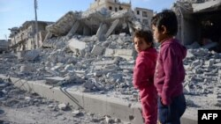 Children stand in a destroyed street in the northwestern border town of Al-Bab on February 23.