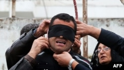 Using her legal right to pardon, the mother (R) of Abdolah Hosseinzadeh, murdered in 2007, removes the noose from the neck of Balal, her son's killer, moments before execution, April 15, 2014
