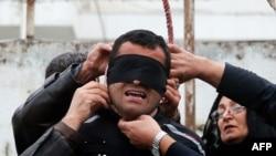 Мать убитого Балалом подростка снимает с приговоренного к смертной казни Балала черную повязку.