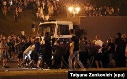 Протестующие в Минске окружили автозак, который через несколько секунд тронется с места с одним из них, зацепившимся за кабину