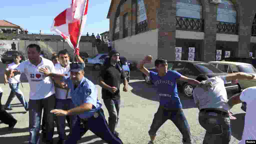 A policeman (center) tries to stop supporters of the ruling National Movement Party as they scuffle with advocates of the opposition Georgian Dream coalition during an election rally in the town of Signagi on September 26. (Reuters)