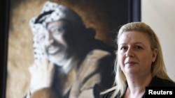 Suha Arafat poses in front of a portrait of her late husband, Palestinian leader Yasser Arafat, before watching a wreath-laying ceremony after her husband's exhumation in the West Bank city of Ramallah in November 2012.