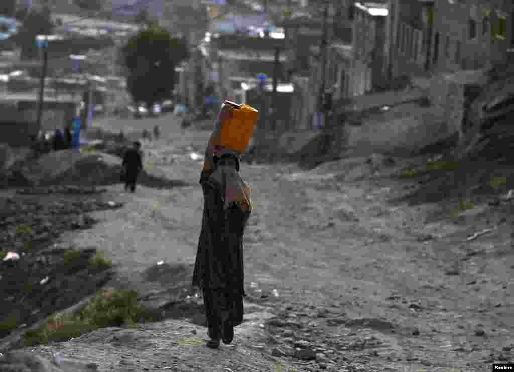 An Afghan girl carries a water container on her head in Kabul on June 5 (Reuters/Omar Sobhani)
