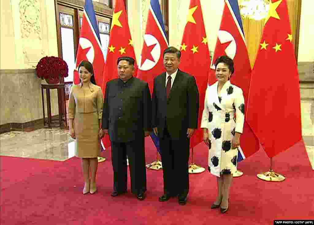 Ким Чен Ын мен әйелі Ри Соль Чжу Пекинде Қытай басшысы Си Цзиньпинмен кездескен сәт.