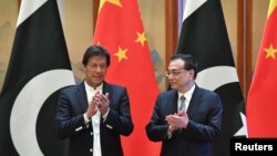 FILE: Pakistani Prime Minister Imran Khan claps with Chinese Premier Li Keqiang during a signing ceremony in April.