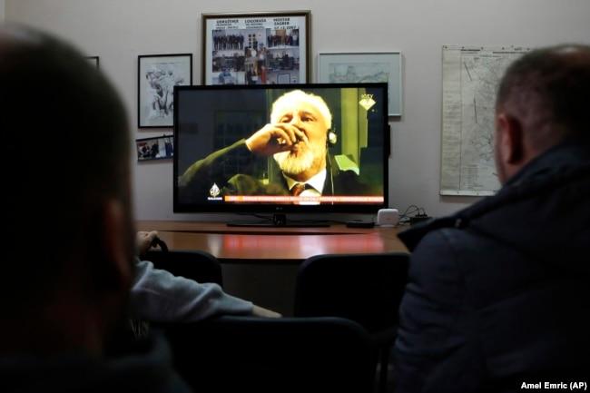 Жители Боснии смотрят в прямом эфире трансляцию из зала суда МТБЮ, во время которой бывший генерал Пральяк совершает самоубийство