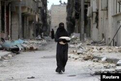 Женщина посреди руин в сирийском городе.