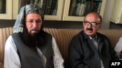Tehrik-e Taliban Pakistan committee member and senior religious party leader Maulana Sami-ul-Haq (left) holds talks with special assistant to Pakistan's prime minister Irfan Siddiqui during a meeting in Akora Khattak on March 5.