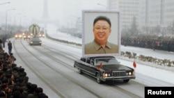 Траурная процессия во главе с лимузином, на котором установлен портрет Ким Чен Ира. Пхеньян, 28 декабря 2011 года.