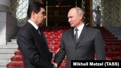 Russian President Vladimir Putin (right) and Turkmen President Gurbanguly Berdymukhammedov meet in Ashgabat on October 2.