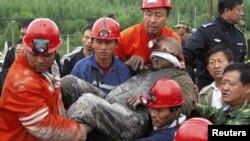 Апат болған шахтадан құтқарылған адамды көтеріп әкеле жатыр. Хэйлунцзян провинциясы, Қытай, 30 тамыз 2011 жыл. (Көрнекі сурет)