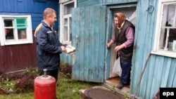 An employee of the Mingas Belarus gas company speaks with a woman as he makes a gas delivery to her house in a Minsk suburb today.