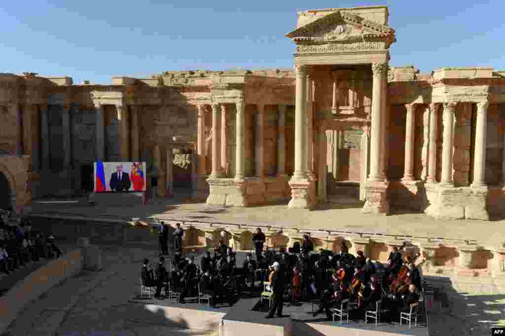 "Russian conductor Valery Gergiev leads a concert in the amphitheater of the ancient city of Palmyra, Syria. Russian President Vladimir Putin spoke live via a video link, just a month after Russian air strikes helped push Islamic State militants from the city. British Foreign Secretary Philip Hammond slammed the concert as ""a tasteless attempt to distract attention from the continued suffering of millions of Syrians."" (AFP/Vasily Maximov)"