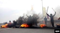 Ирак армиясы Анбар провинциясында баштаган операцияга жооп кылып, сунни согушчандары кан жолдо дөңгөлөктөрдү өрттөөдө. 30-декабрь 2013-жыл.