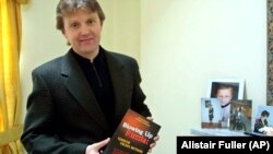 Aleksandr Litvinenko poses with his book Blowing Up Russia: Terror From Within at his home in London in May 2002.