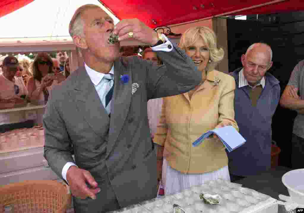 Britain's Prince Charles samples a raw oyster as Camilla, the Duchess of Cornwall, looks on during a visit to the Whitstable Oyster Festival in Whitstable, England. (AFP/Arthur Edwards)