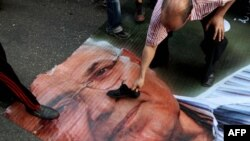 An Egyptian protester puts his shoe on a ripped poster of presidential candidate Ahmed Shafiq in Cairo in June.
