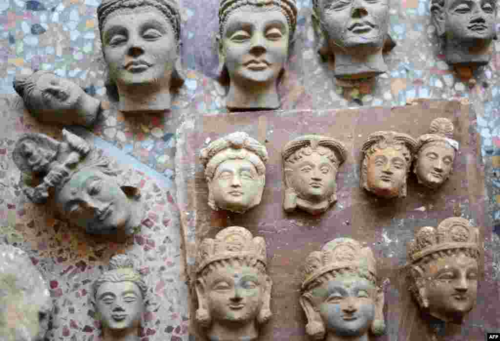 An original Buddha head (center top) sits among recently made copies at Taxila in Punjab Province in Pakistan.