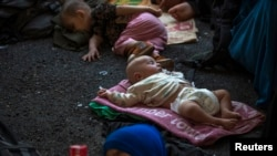 Children of Uyghurs from China's western region of Xinjiang rest inside a temporary shelter in Thailand.