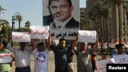 Участники протеста против правления Мухаммеда Мурси несут плакат с фотоколлажем из портретов Мурси и бывшего президента Египта Хосни Мубарака. Каир, 28 июня 2013 года.